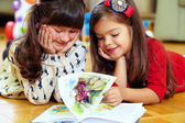 Two beautiful little girls reading book at home — Foto de Stock