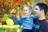 Smiling father and son on autumn tree backgroung — Stock Photo