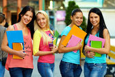 Four beautiful college students posing on city street — Stock Photo