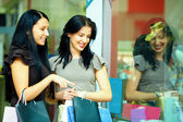 Two elegant women look in clothes store showcase — Stock Photo