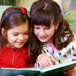 Two beautiful girls reading book at home - Stock Photo