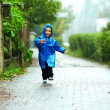 Stock Photo: Happy baby boy running the street under the rain