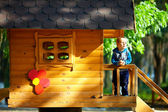 Cute baby boy playing in tree house, sunny outdoor — Stockfoto