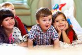 Groep van gelukkige jonge geitjes kijken tv thuis — Stockfoto