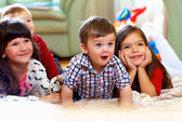 Group of happy kids watching tv at home — Stock fotografie