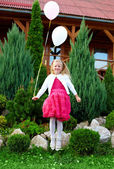 Beautiful princess girl fly with balloons, green outdoors — Stock Photo