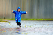 Happy baby boy running the street, rainy weather — Stock Photo