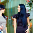 Two beautiful smiling women walking the mall and talking — Stock Photo