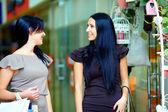 两个漂亮的微笑着女人走路购物中心和说话 — 图库照片