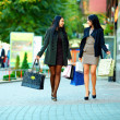 Happy women walking the city street with shopping bags — Stock Photo