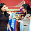Two happy women shopping in clothes store — Стоковая фотография