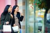 Two happy elegant women looking in shop window — Stock Photo
