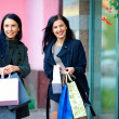 Smiling girls shopping in the city — Stock Photo