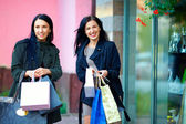 Smiling girls shopping in the city — Photo