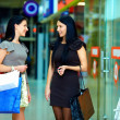 Smiling female friends shopping in the city mall — Stock Photo