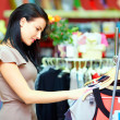 Pretty elegant woman shopping in clothes store - Stock Photo