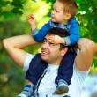 Father and son having fun playing in green park — Stock Photo