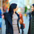 Two happy women talking on crowded city street — Stock Photo #17670431