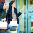 Two female friends looking into the shop window — Stock Photo