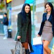 Happy girls with shopping bags in city street — Stock Photo