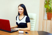 Smiling woman at working place in office interior — Stock Photo