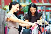 Elegant women shopping in retail clothing store — Stock Photo