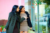 Two excited elegant women looking in shop window — Stock Photo