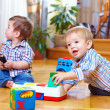 Two baby boys playing with toys at home — Stock Photo #18096743