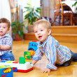 Two cute baby boys playing with toys at home — Stock Photo #18096745