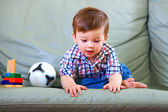 Curious little baby boy on couch — Stock Photo