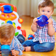 Two little baby boys drinking from feeding bottle, home interior — Stock Photo #18119123