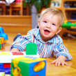 Cute baby boy playing with toys in living room — Stock Photo #18123237