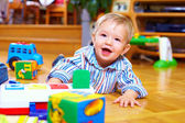 Cute baby boy playing with toys in living room — Stock Photo
