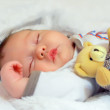 Adorable baby newborn sleeping with toy — Stock Photo