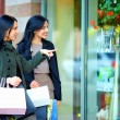 Happy girls with shopping bags pointing finger in the shop window — Stock Photo #18237039