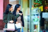Happy girls with shopping bags pointing finger in the shop window — Stock Photo