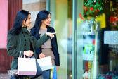 Niñas felices con bolsas de compras de señalar con el dedo en la ventana de la tienda — Foto de Stock