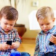 Cute baby toddlers exploring mobile phones - Stock Photo