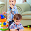 Foto de Stock  : Two cute baby toddlers explore mobile phones at home
