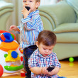 Two cute baby toddlers explore mobile phones at home — Stock Photo