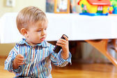 Curious baby toddler exploring mobile phone — Stock Photo
