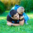 Father and son having fun in green park — Stock Photo