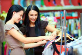 Two smiling woman shopping in retail store — Stok fotoğraf