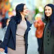 Happy female friends walking the crowded city street — Stock Photo