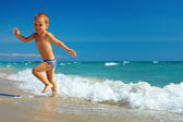 Happy baby running from surf on the beach — Stock Photo
