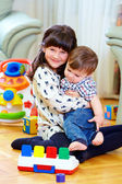 Elder sister playing with little brother at home — Stock Photo