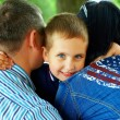 Happy boy hugging parents — Stock Photo #19646157