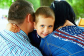 Happy boy hugging parents — Stock Photo