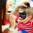 Woman painting face of kid outdoors — Stock Photo #19668037