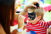 Woman painting face of kid outdoors — 图库照片